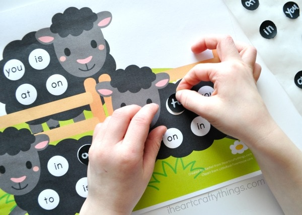Child placing the matching sight word sticker on the printable.