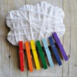 Square image of yarn wrapped cloud and rainbow painted clothespins attached to it sitting on a faux wood background.