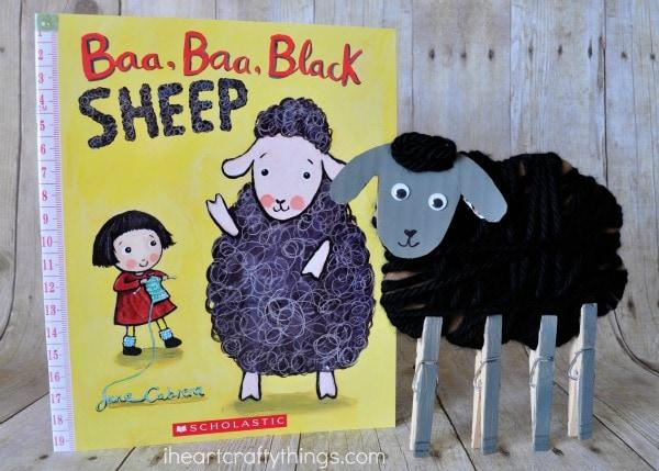 "Yarn wrapped sheep craft standing next to book titled ""Baa Baa Black Sheep""."