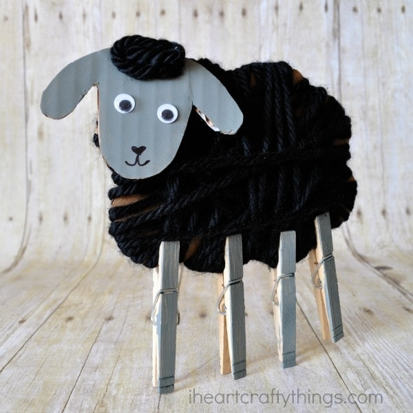 Square image of yarn wrapped cardboard sheep craft with clothespins as legs, standing up on faux wood background.