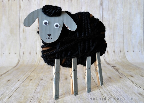Vertical image of yarn wrapped sheep craft with clothespin legs standing on faux wood background.