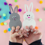 Adults with their fingers in two bunny finger puppets, one white bunny and one gray bunny, with a pink out of focus background with colored poms scattered around.
