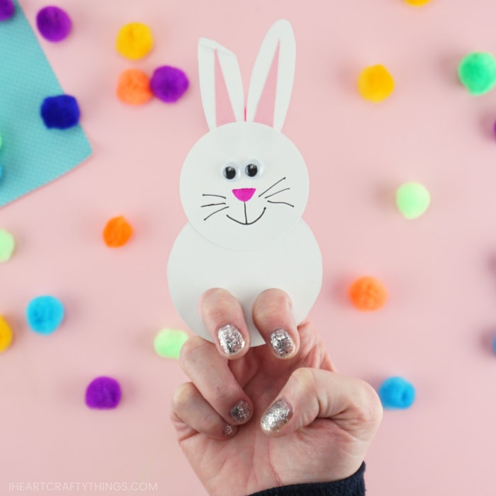 Close up image of a white bunny finger puppet with an adult showing how to place your fingers inside the puppet to play with it.