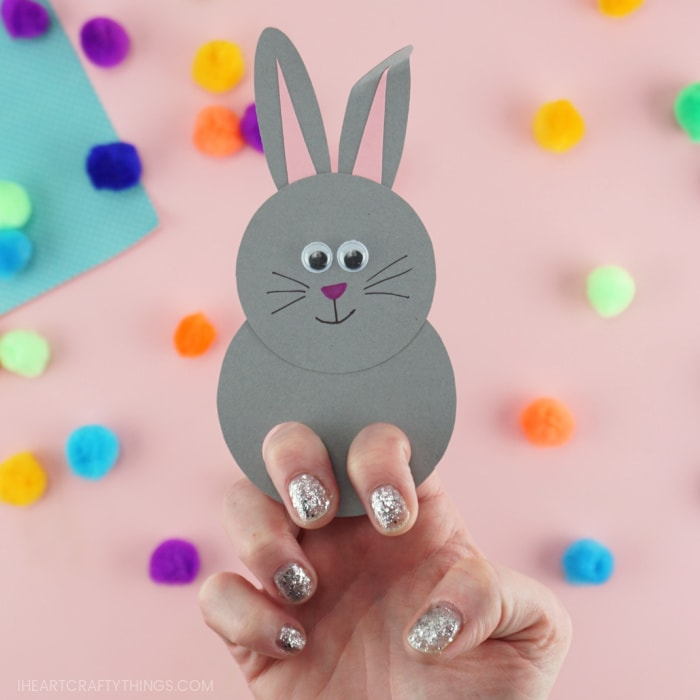 Close up image of a finished gray bunny finger puppet with an adult placing two finger in the holes, showing how to play with the puppet.