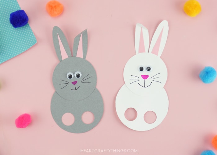 A gray bunny puppet and a white bunny puppet laying next to each other on a pink background with colored poms scattered around.