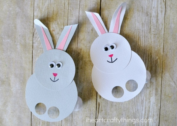 One gray bunny finger puppet and one white bunny finger puppet laying flat on a faux wood background.