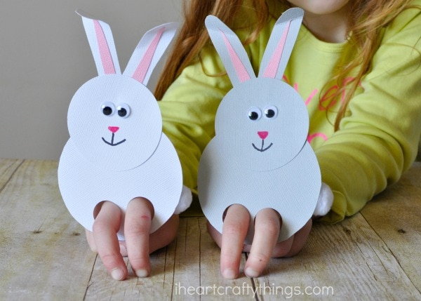 Child playing with bunny finger puppets, one white and one gray.