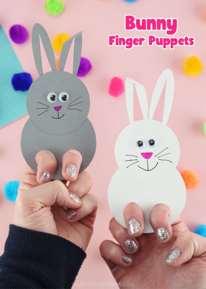 """Vertical close up image of an adult showcased two finished bunny puppets, one white and one gray, with the text """"bunny finger puppets"""" in the top right corner."""