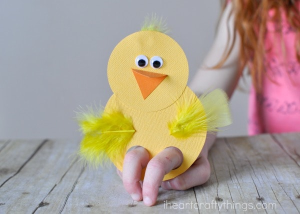Horizontal image of child playing with a chick finger puppet.