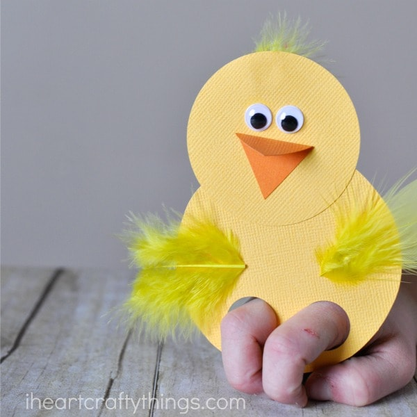 Close up image of child playing with the chick finger puppet made out of paper and yellow feathers.