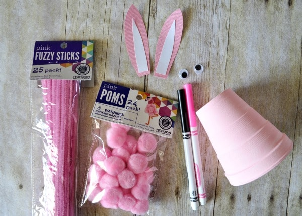 supplies needed to make the foam cup bunny craft laid out on a faux wood background.