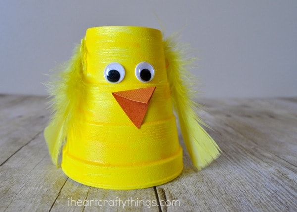 Close up horizontal image of yellow painted foam cup made into a chick craft for kids.