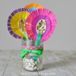 close up image of mother's day flower bouquet gift made out of wooden spoons and cupcake liners in a mason jar.