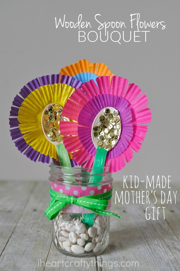 """Vertical close up image of flower bouquet in a mason jar with the words """"wooden spoon flower bouquet"""" in the top right corner and """"kid-made mother's day gift"""" in the bottom right corner."""
