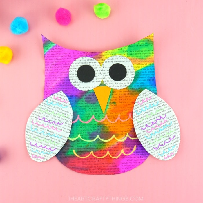 Painted newspaper owl craft laying on a pink background with craft pom poms scattered around.