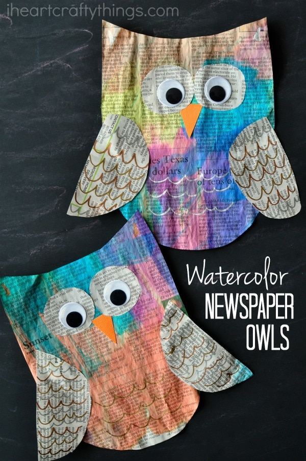 """Vertical image of two painted newspaper owl crafts laying one on top of the other with the words """"watercolor newspaper owls"""" in the bottom right corner."""