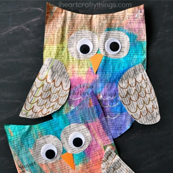 Two painted newspaper owl crafts, one laying on top of the other on a black chalkboard background.