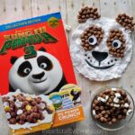 Box of Kung Fu Panda cereal laying next to a bowl of the cereal and a completed panda craft.