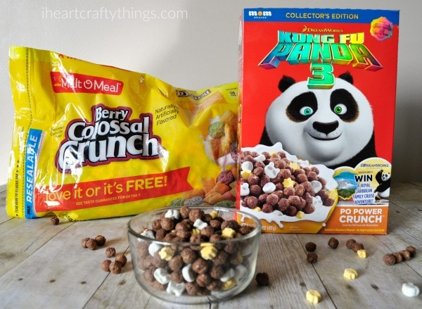 Box of Kung Fu Panda cereal and a bag of Berry Colossal Crunch cereal with a bowl full of cereal and some scattered around a faux wood background.
