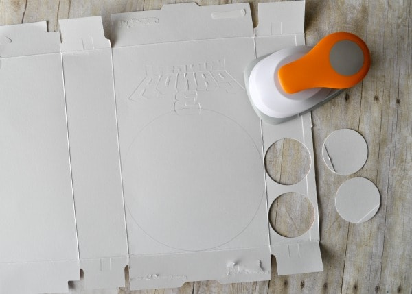 Unfolded cereal box with a circle punch punching circles out of the cardboard to make the panda craft.