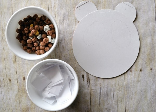 Cereal box panda shape laying on a faux wood background with a bowl of white tissue paper and cereal ready to make the craft.