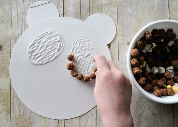 Child gluing cereal on the cardboard panda shape.