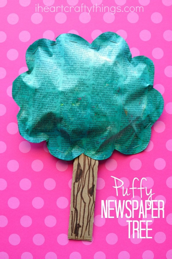 vertical image of puffy newspaper tree craft on a pink background.