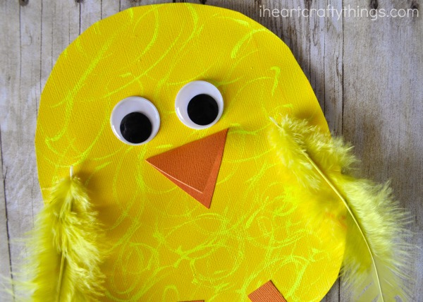 Close up image of where to glue the googly eyes, folded beak and yellow feathers on the chick craft.