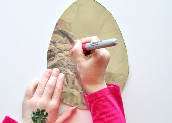 Child using a sharpie to decorate a tin foil covered cardboard Easter Egg shape.