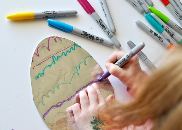 Child using a purple Sharpie marker to decorate a tin foil covered cardboard Easter Egg shape.