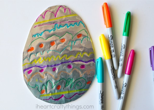 Blue, yellow, orange, green and pink Sharpie markers laying next to a decorated tin foil Easter Egg.