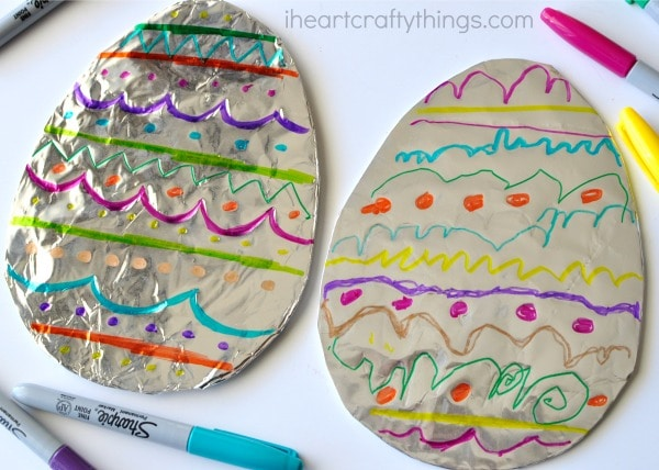 Side angle of two decorated tin foil Easter eggs laying next to each other.
