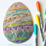 Blue, yellow and orange Sharpie marker laying next to a tin foil covered cardboard Easter egg decorated with the markers.