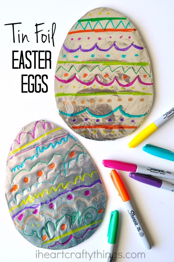 """Vertical image of two decorated tin foil Easter Egg art projects laying one on top of the other with Sharpie markers scattered around them and the words """"Tin Foil Easter Eggs"""" in the top left corner."""