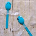 close up image of two wooden spoon dragonflies .