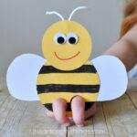 close up image of child using their fingers to play with a bee finger puppet