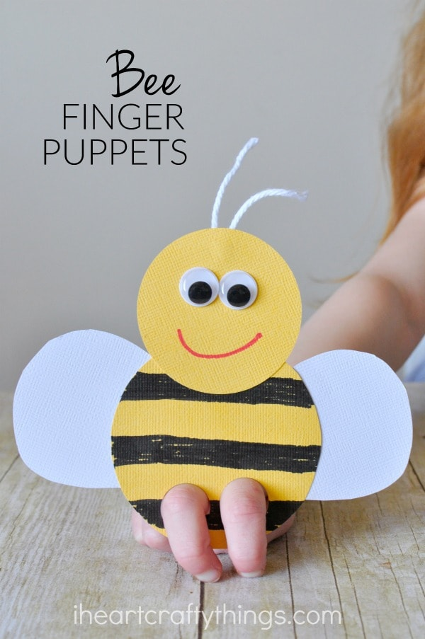 "vertical image of child playing with a bee puppet with the words ""bee finger puppets"" in the top left corner."