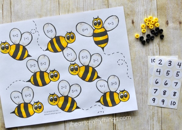 Printed bumblebee preschool math printable laying out with number stickers and black and white pony beads.