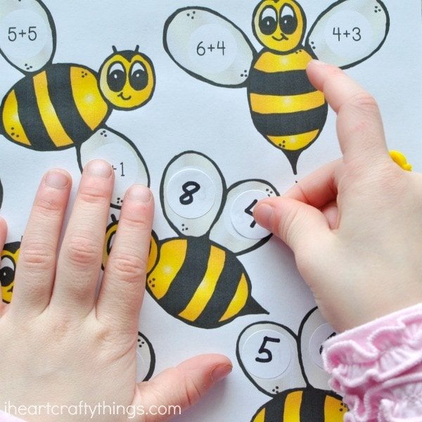 close up image of child placing a sticker on the bumblebee math printable