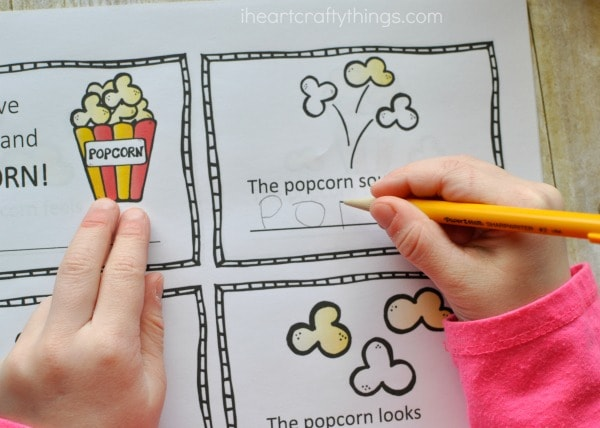 Child using a pencil to fill in the writing prompts in the five senses mini book.