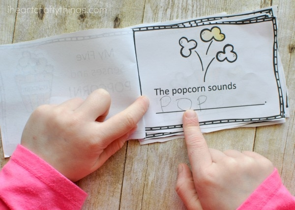 Preschool child using their finger to point to words and read the fives senses mini book.
