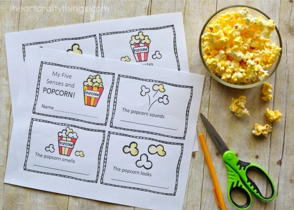 Printed out fives senses mini book with popped popcorn in a bowl next to it and scissors and a pencill