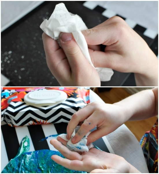 child using Huggies wipe to wipe off their hands after making their marbled art project