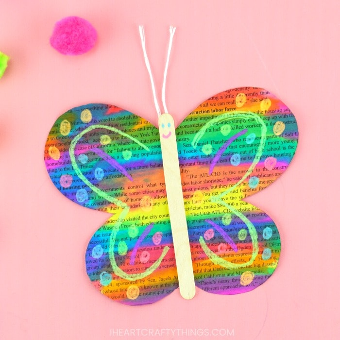 Close up square image of painted newspaper butterfly craft laying on a pink background with a pink pom pom scattered in the background.