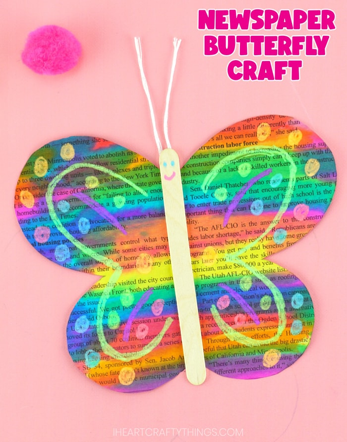 """Close up vertical image of butterfly craft laying on a pink background with the words """"newspaper butterfly craft"""" in the top right corner."""