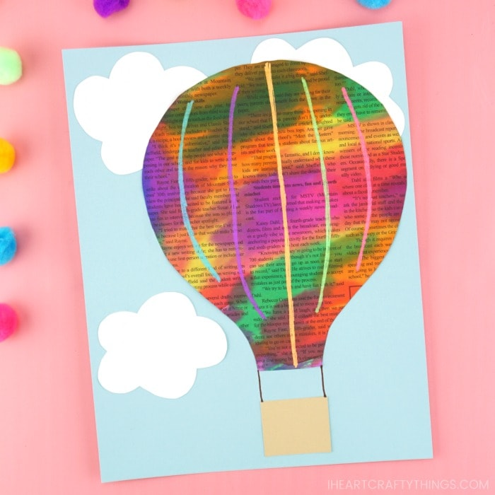 Painted newspaper hot air balloon craft laying on a pink background with craft poms scattered around.