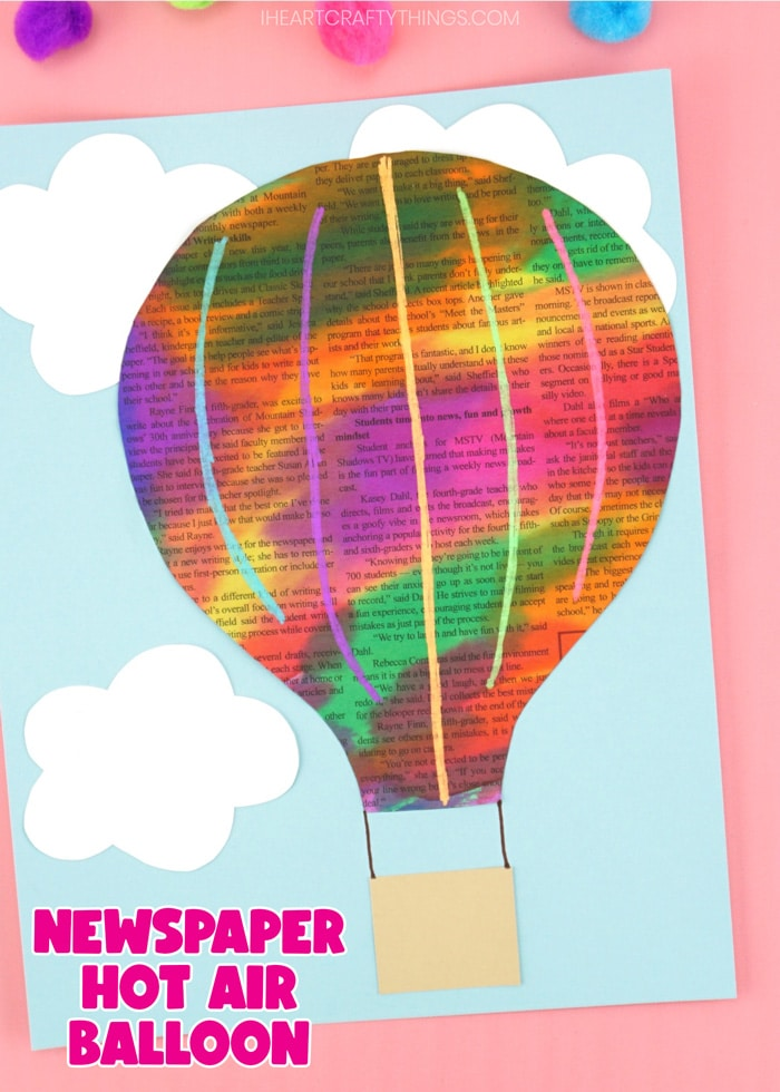 "Close up vertical image of finished craft on a pink background with the words ""newspaper hot air balloon"" in the bottom left corner."