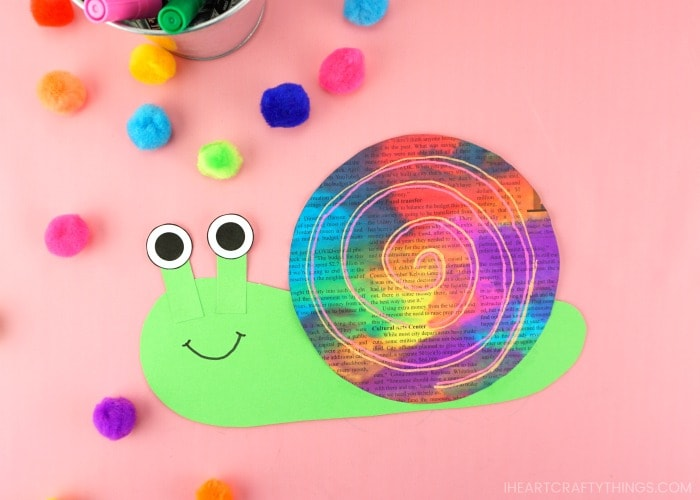 Horizontal image of finished newspaper snail craft laying on a pink background with colored craft pom poms scattered around in the background.