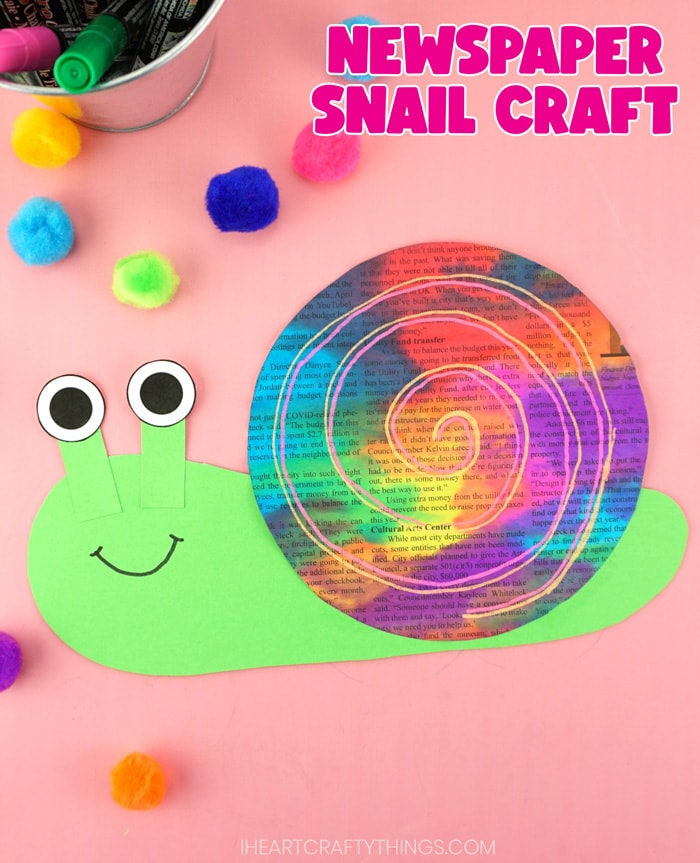 "Vertical close up image of finished snail craft laying on a pink background with colored craft poms scattered around and metal tin of chalk markers in the top left corner. Words ""Newspaper snail craft"" are in the top left corner."
