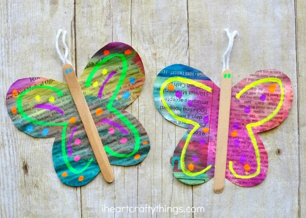 two painted newspaper butterfly crafts laying on a faux wood background